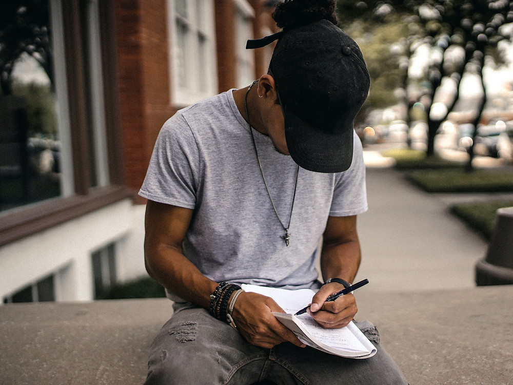 young man sitting down writing in a notebook