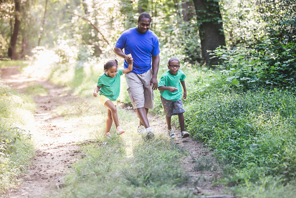 A man holding hands with his two kids on a walk in the woods