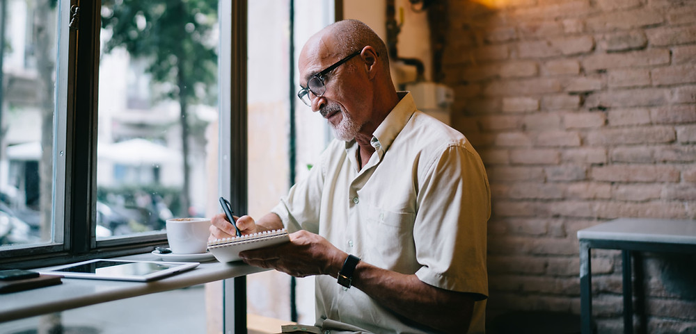 Man at a café writing in the journal
