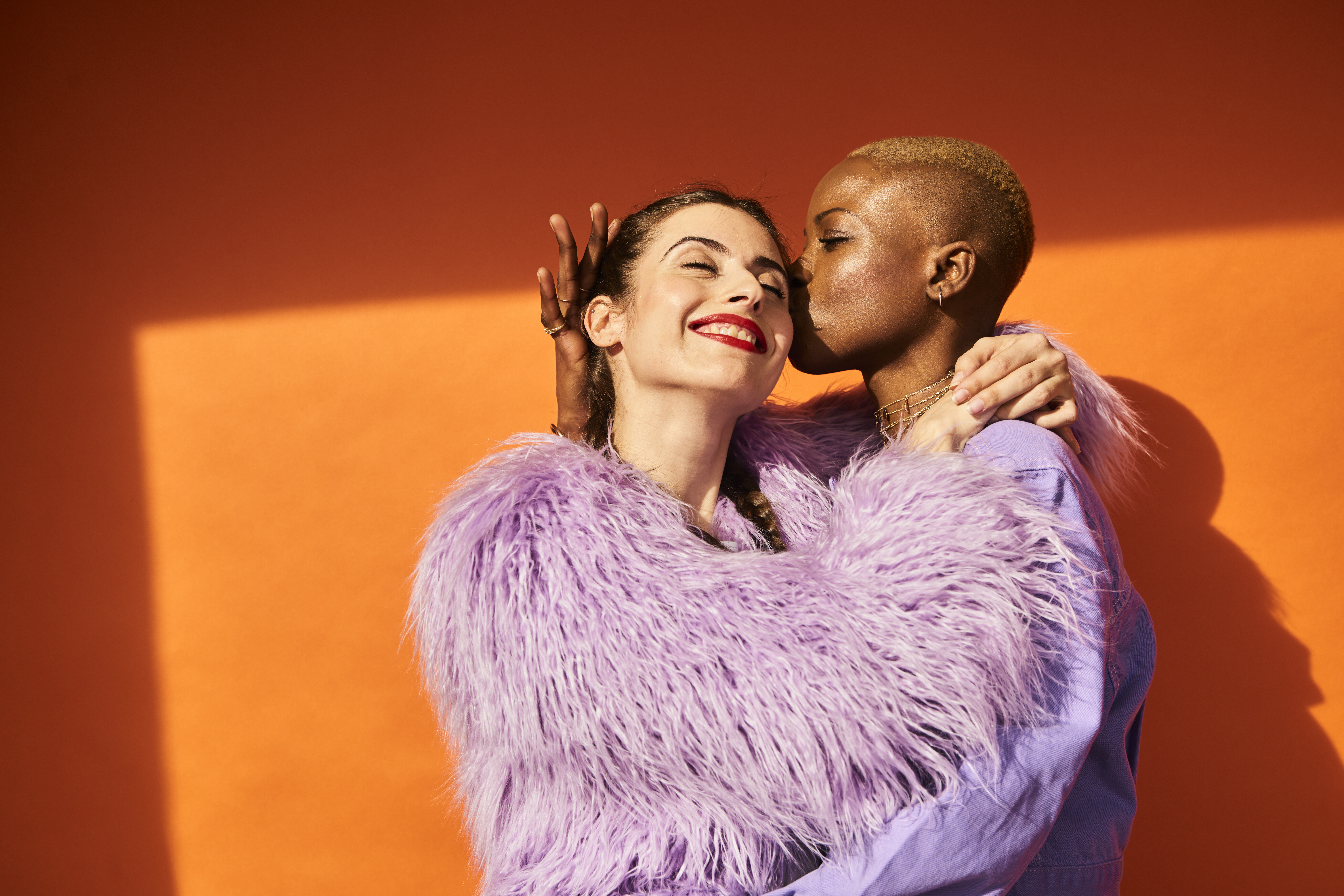 An interracial queer couple kiss in front of an orange background