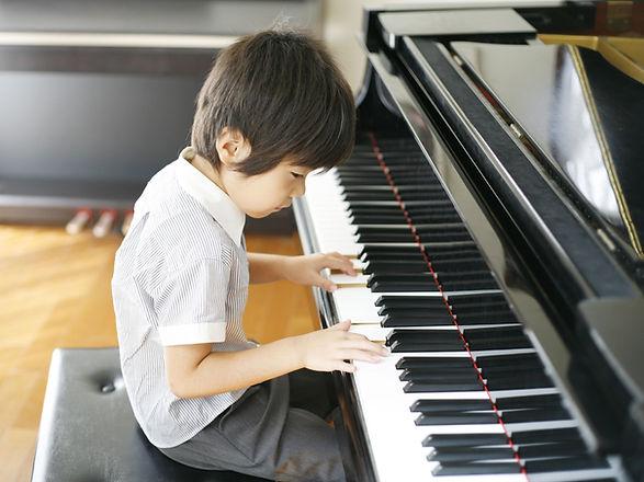 Jonge jongen piano spelen