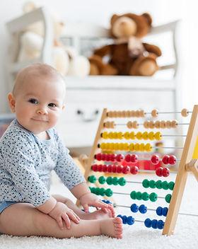 Baby spielt mit Rechenschieber