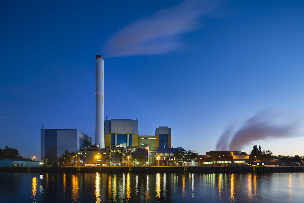 Photograph of a factory by the bank, taken in the evening.