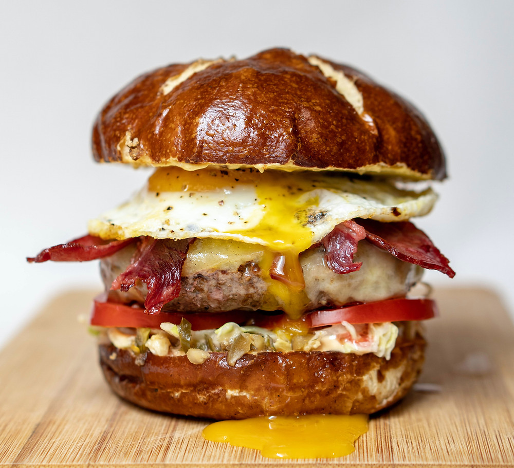 A very greasy hamburger with a fried egg and a pretzel bun
