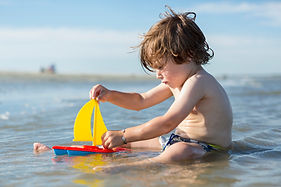 Boy Playing with Toy Boat