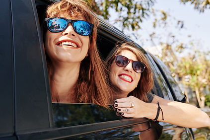Two women in car, smiling out window. There is hope to feel better after anxiety treatment in St. Louis, MO 63011. Marble Wellness can provide counseling for anxiety. We offer in-person sessions, telehealth in Missouri, and park therapy too!