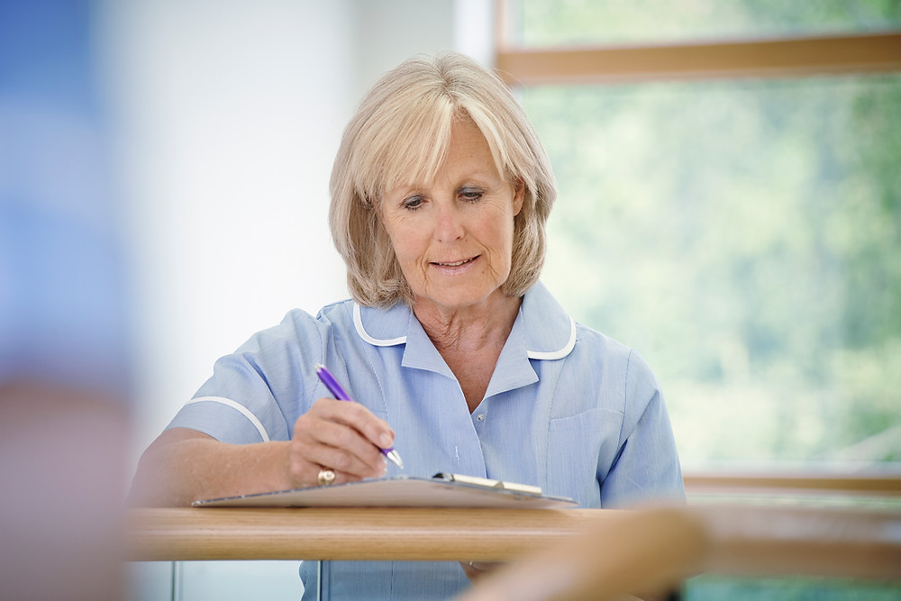 Nurse or midwife filling in a form