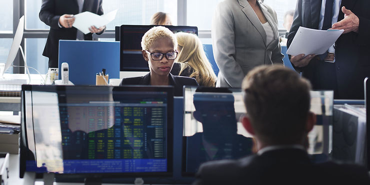 A woman sitting by her computer in a trading room