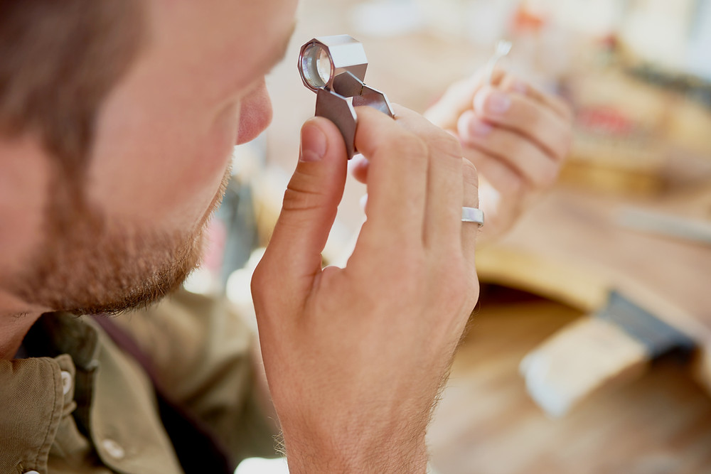 A jewellery appraiser inspecting a piece of jewellery using a loupe