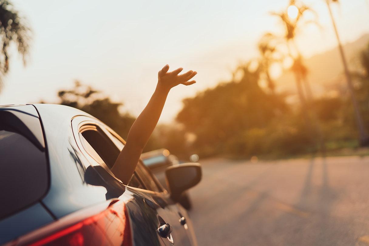 Main agitant hors de la voiture
