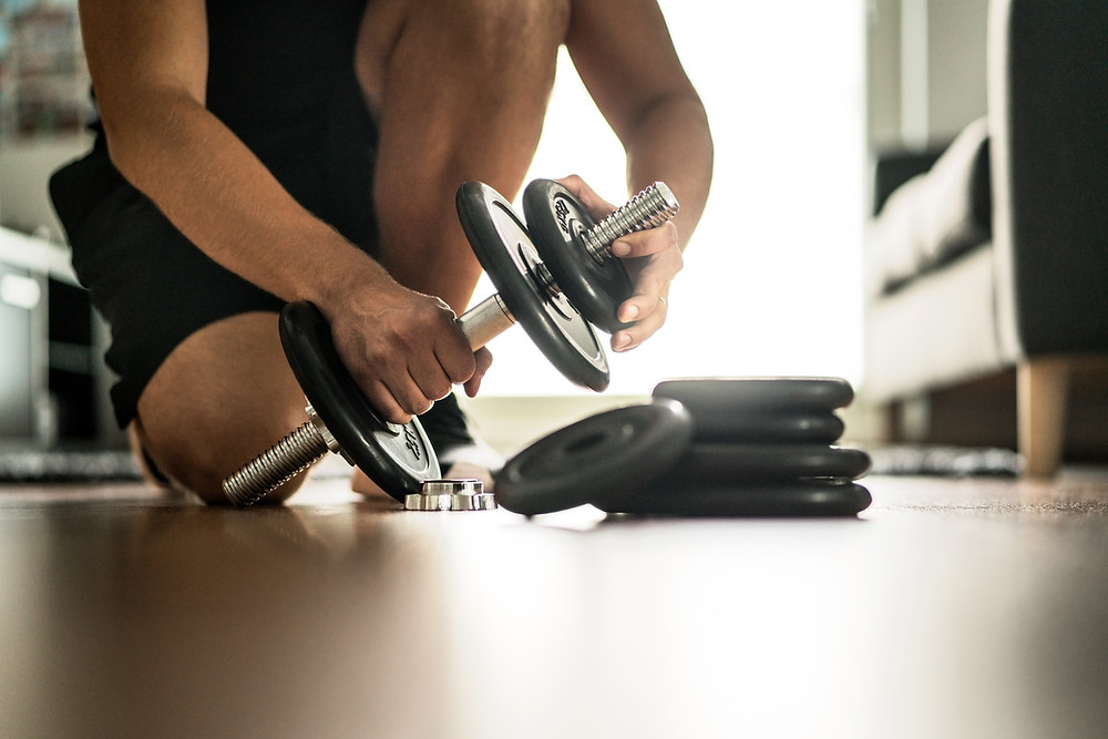 A man in his home gym is adding weight to his adjustable dumbbells.