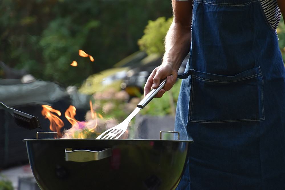 man holding grilling tools