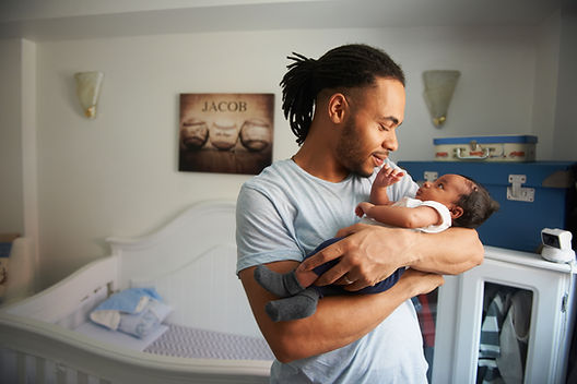 Black person presenting as a man holding a Black baby in a nursery because PMADs affect people of all genders.
