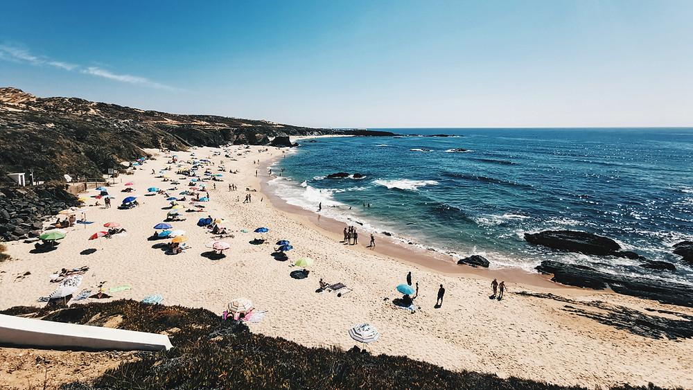 People on sandy beach by ocean