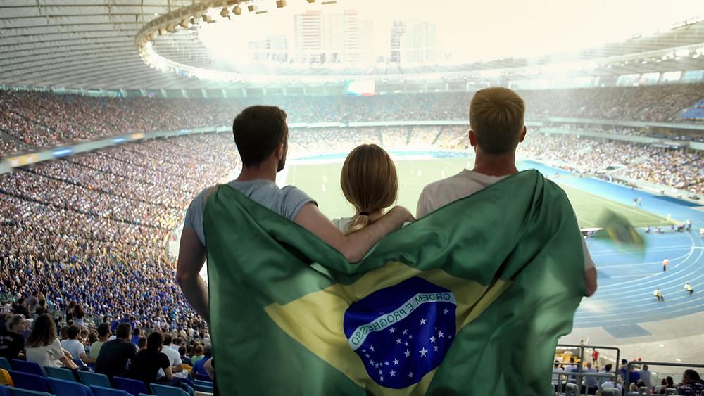 3 amigos em um estádio de futebol com a bandeira do brasil