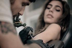 Garota recebendo tatuagem de braço
