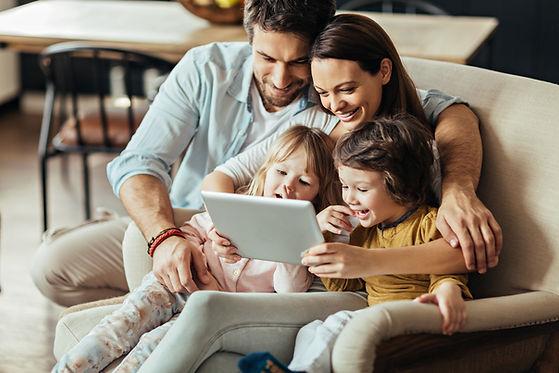 Perhe lukee tabletin näyttöä yhdessä sohvalla.