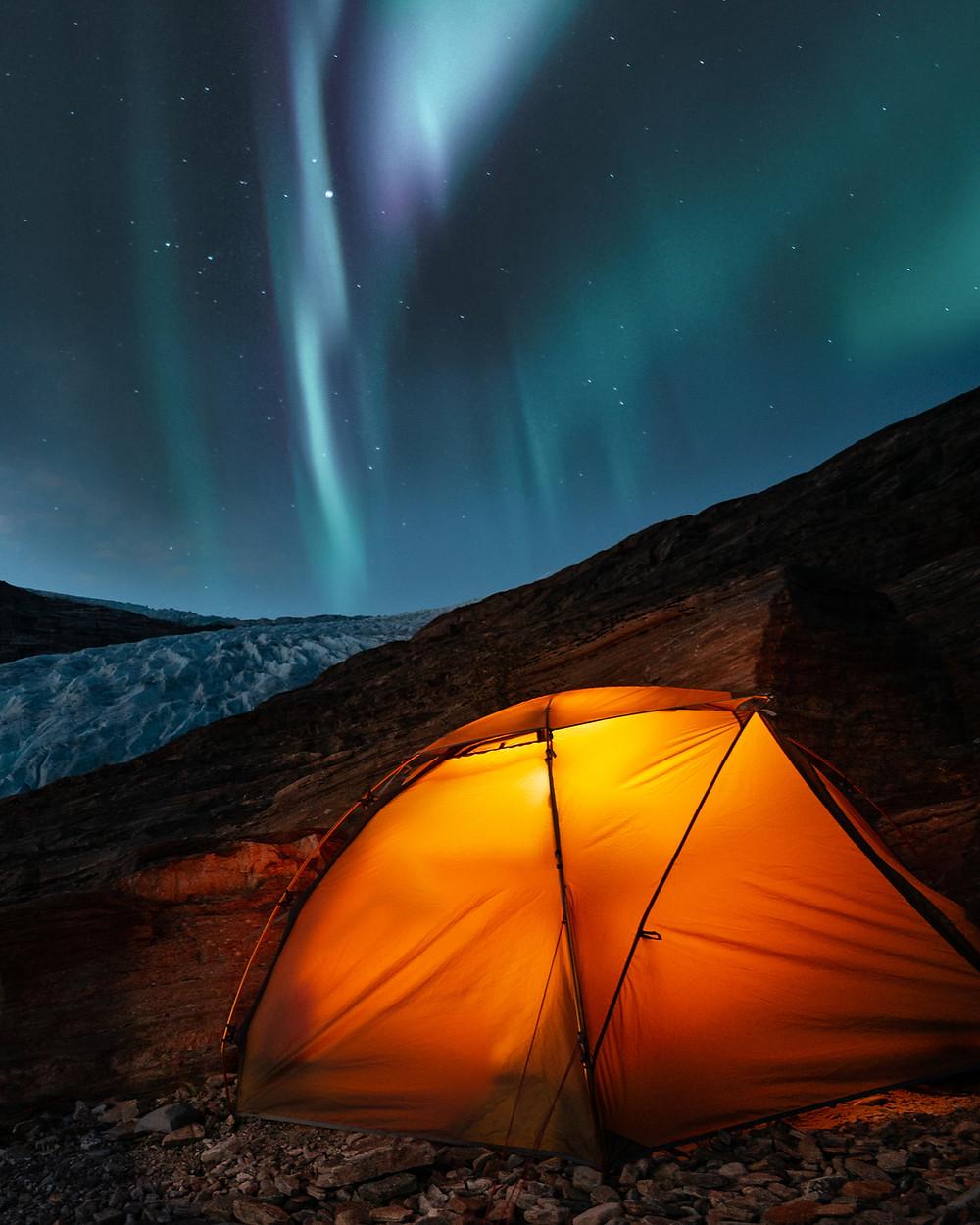 A starlit black night sky with glowing wisps of greenish white light streak across the sky above a glowing tent in a night dark, wilderness landscape.