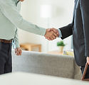 中年夫婦と握手するビジネスマン