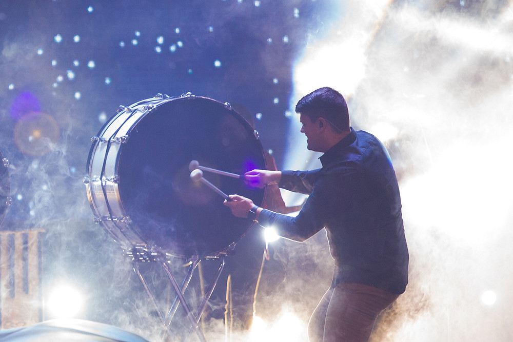 A man playing on a large drum on a stage