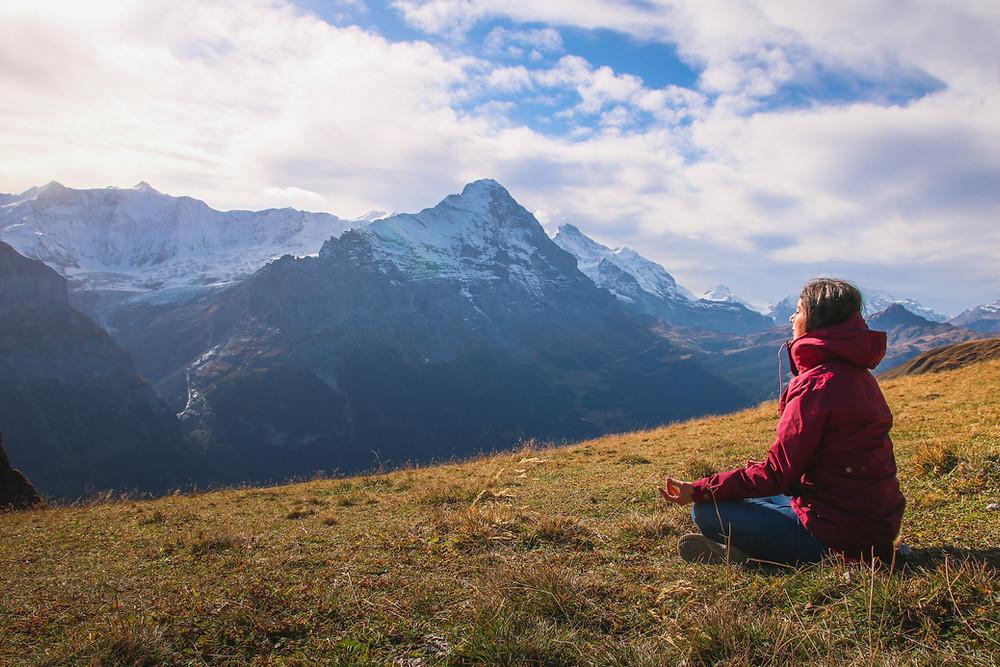 Woman meditating on a hillside amid mountains