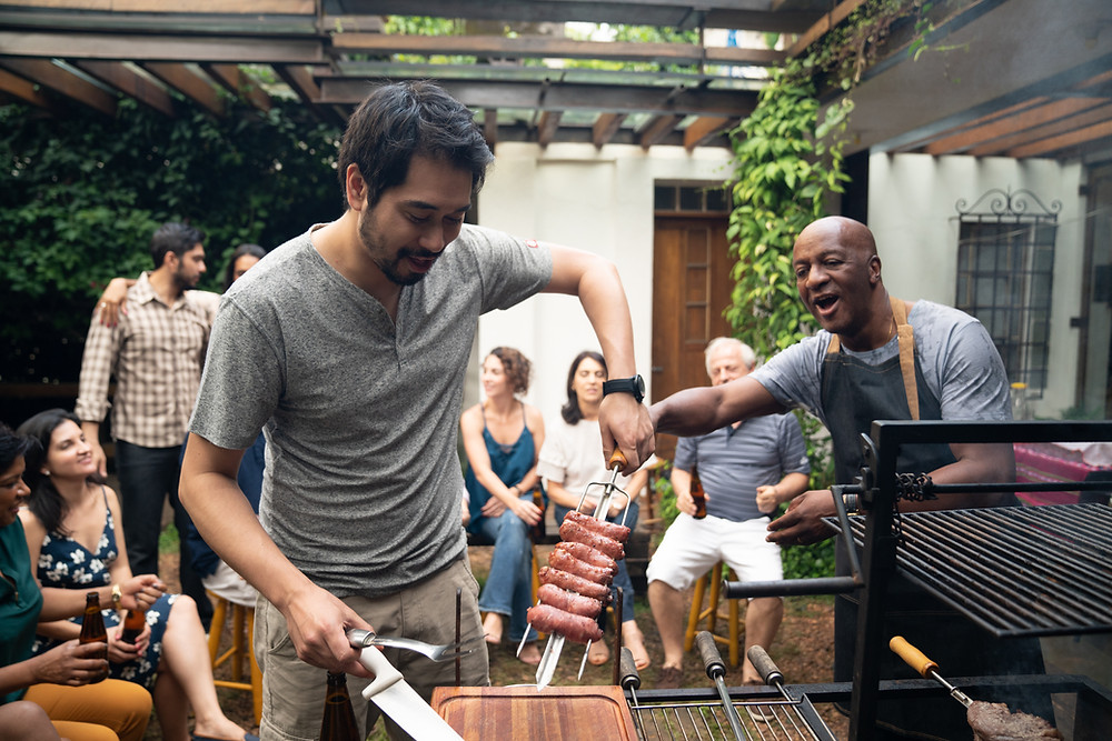 Two men grilling at a party with other adults behind them enjoying the cookout. Making friends as an adult is hard. Follow these tips to help change your mindset about making new friends and gaining some traction on increasing your social satisfaction! Marble Wellness is here for you if you are experiencing anxiety, depression, grief, maternal overwhelm in St. Louis!