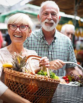 Older man and woman smiling holding baskets with fresh produce