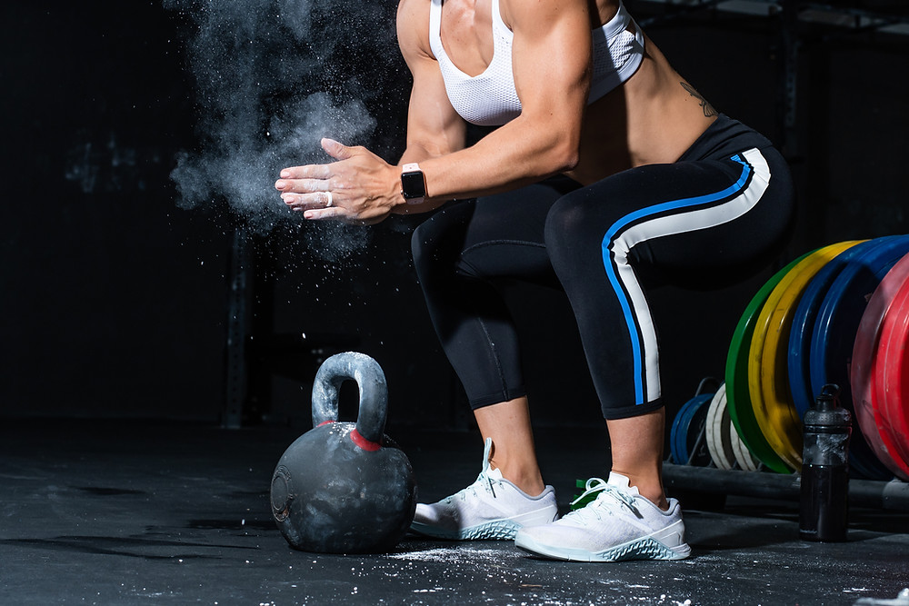 strong woman prepares to perform a set of kettlebell swings during an EMOM training session