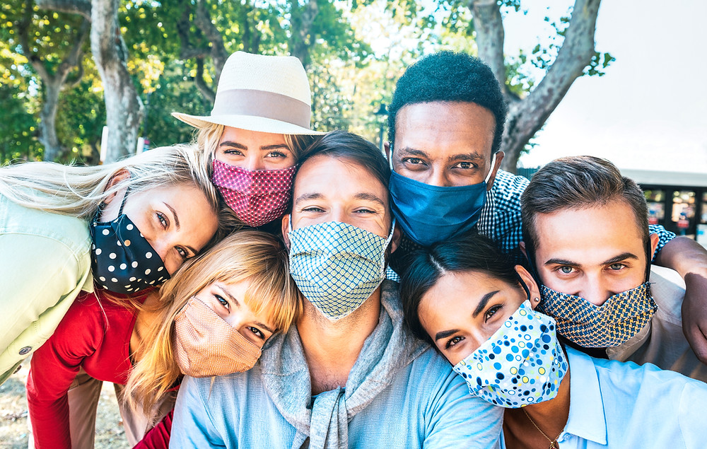 This is a picture of seven people of different races crowded together. All are wearing cloth masks over their faces. There are three white women, one white man, one asian man, one asian woman, and one Black man.