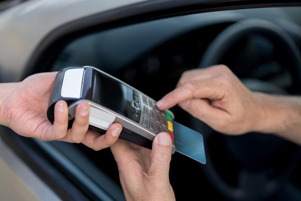 אדם משלם בכרטיס אשראי על תיקון לפטופ