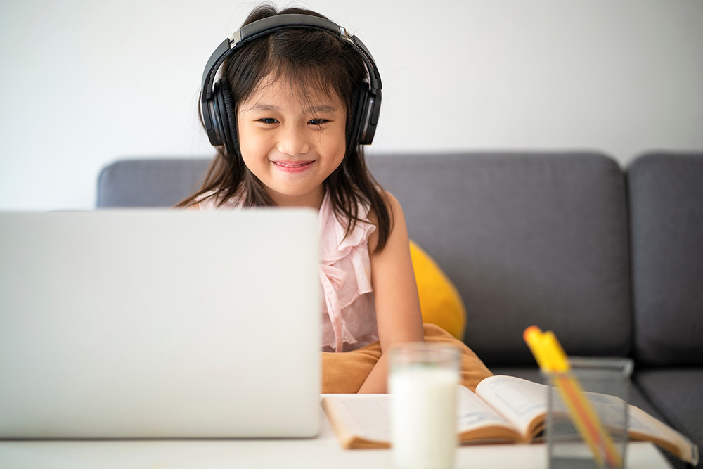A young girl enjoys her learning session using Fast ForWord, a software to help overcome reading difficulties that is accessible through The Key Clinic.