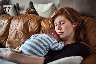 Mother resting holding newborn baby