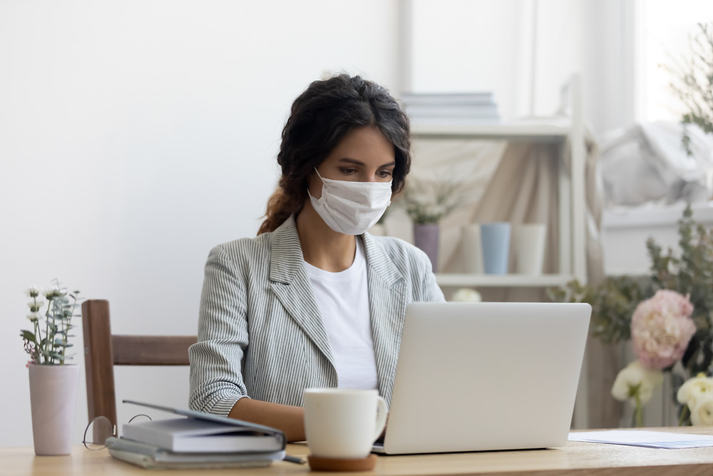 A girl sitting and working on a laptop wearing a mask