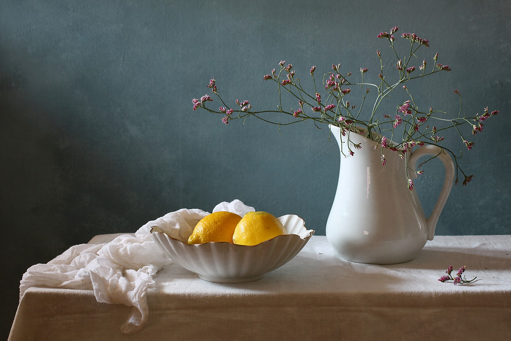 Artistic image of antique ceramic water pitcher and bowl, with flowers in the pitcher and lemons in the bowl. cloth on a table, green background.