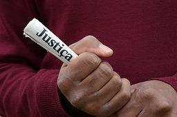 אדם מחזיק פלאייר שעליו רשום צדק