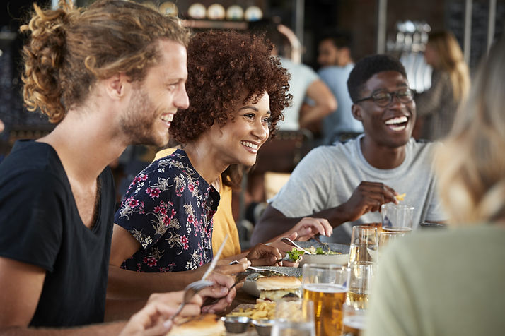 Friends at lunch, smiling and laughing and feeling better after seeing a chronic illness counselor near me for counseling for chronic illness in St. Louis, MO and therapy for chronic pain with online therapy in Chicago, IL.
