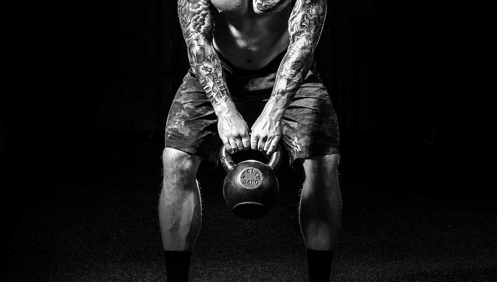 An image of a man swinging a kettlebell. This heads the discussion on the benefit of kettlebell swings which includes grip strength.