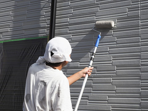 戸建て住宅の外壁を塗る塗装職人