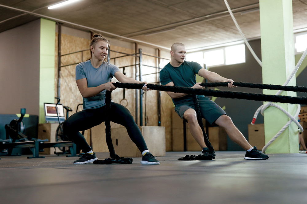 Man and Woman pulling battle ropes. Working Out