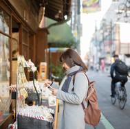 Mujer navegando fuera de una tienda