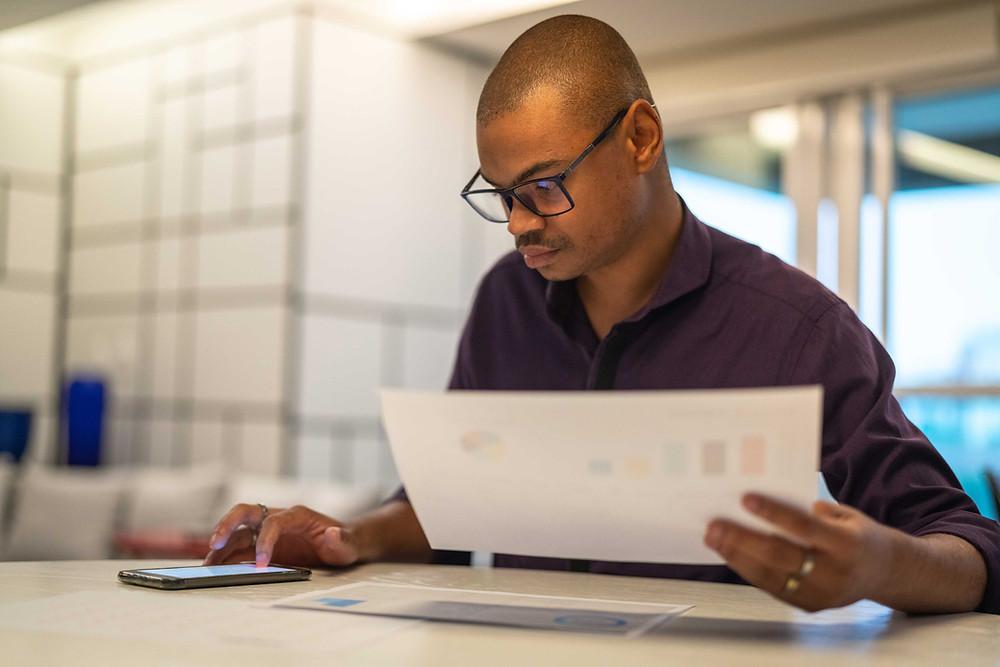 Homem de óculos segurando folha de papel e digitando no celular