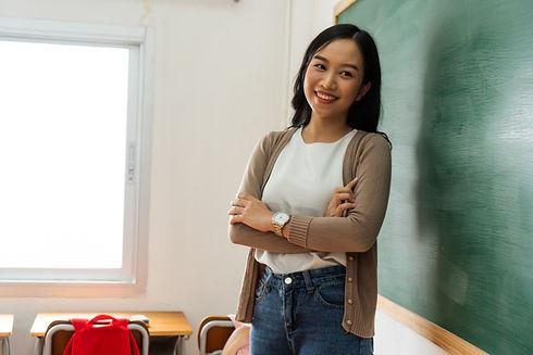Teacher Standing In Front Of Blackboard
