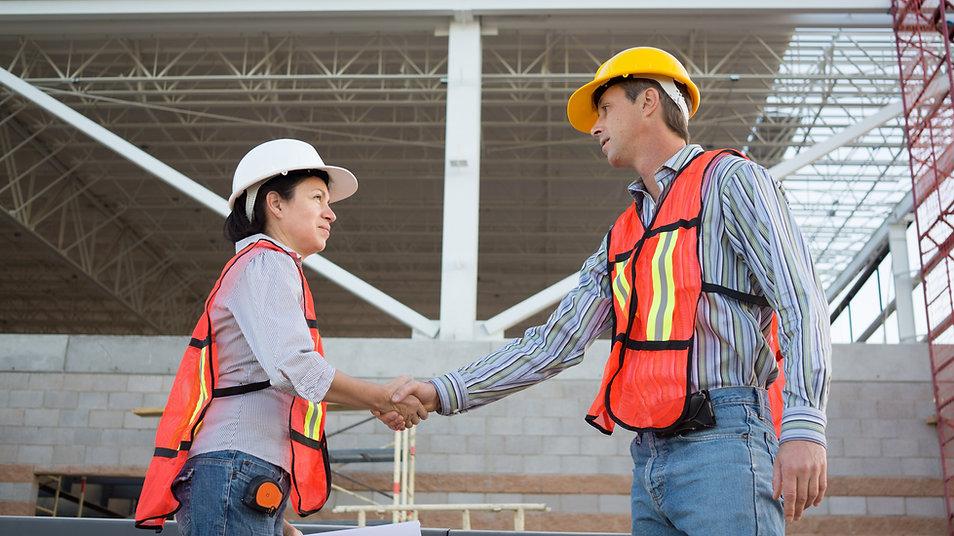 Trabalhadores da construção civil apertando as mãos