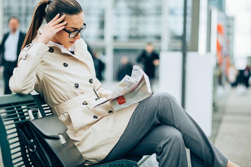 Femme lisant un journal sur un quai de gare