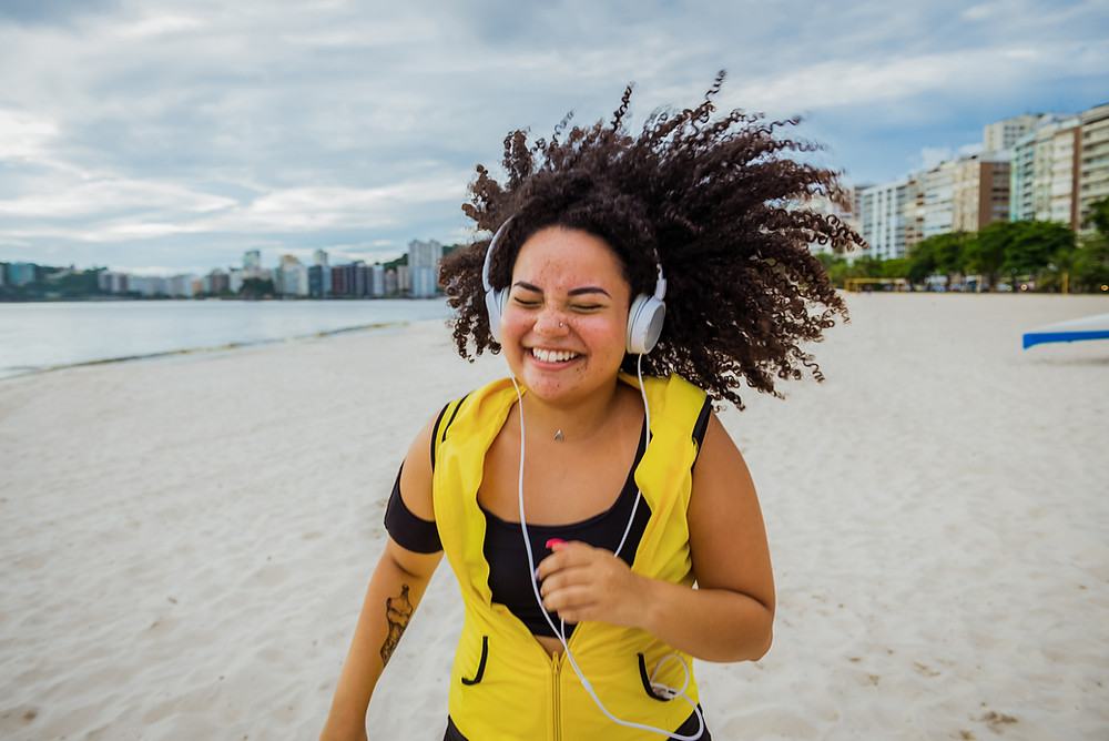 A happy woman running on a beach with headphone ON