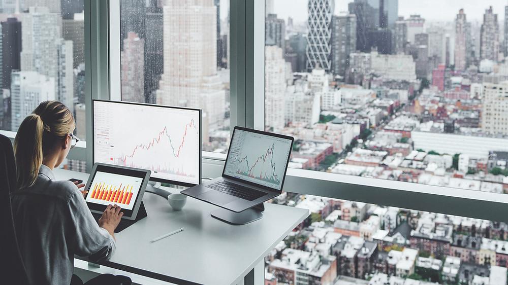 Woman sitting at desk analyzing charts