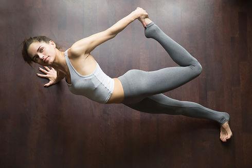 Mulher executando uma Posição de Yoga, praticando Yoga Online ao Vivo