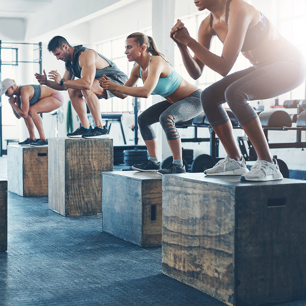 an exercise class preforming the plyometric exercise box jumps.