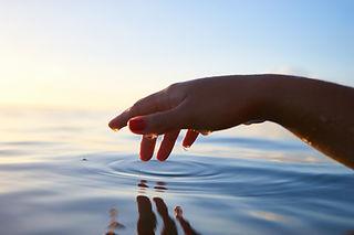 Hand, die Wasser berührt