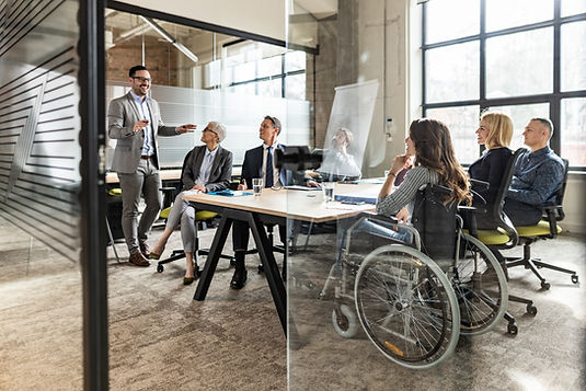 Business meeting in office conference room, 4 people seated in office chair, one female employee with long brown hair seated in wheelchair, one male standing smiling
